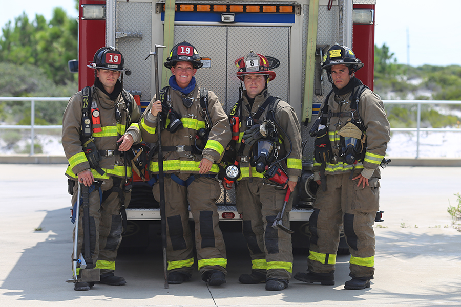 Firefighters stand in uniform by a fire truck