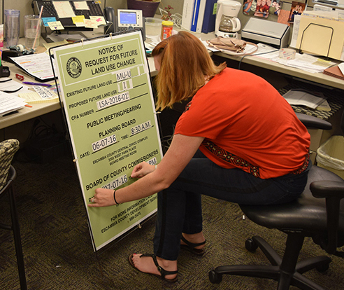 A Planning Board clerk readies a zoning case sign for placement