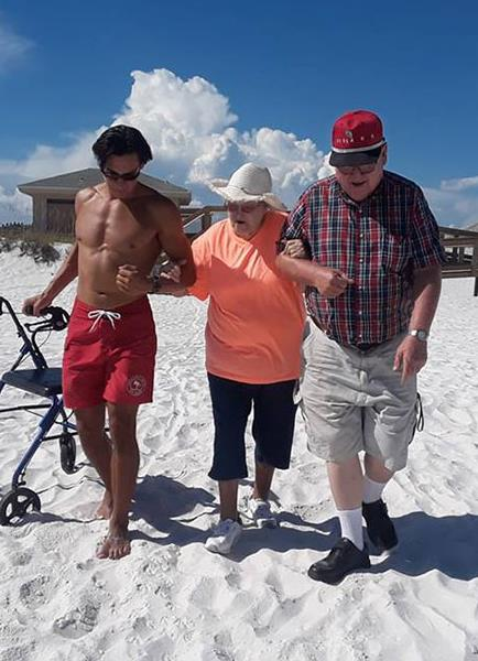 A lifeguard helps a woman along the beach to the Gulf of Mexico
