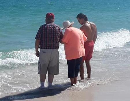 A lifeguard helps an elderly woman dip her toes in the Gulf of Mexico